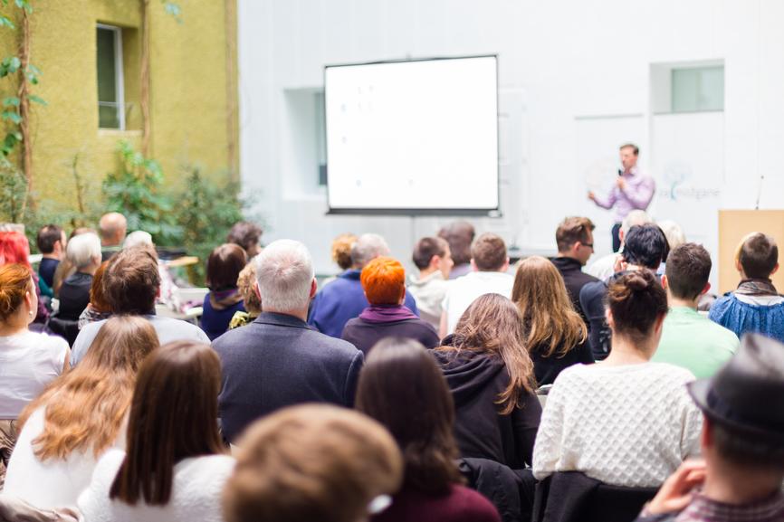 Speaker auf einer Bühne spricht vor einer Gruppe Personen und virtuell mit seinen virtuellen Teilnehmern in der Hybrid Veranstaltungen
